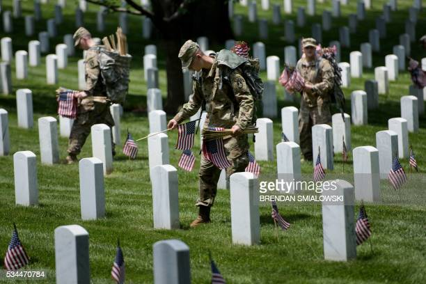 Members of the US Army place American flags at graves at Arlington National Cemetery May 26 2016 in Arlington Virginia in preparation for Memorial...
