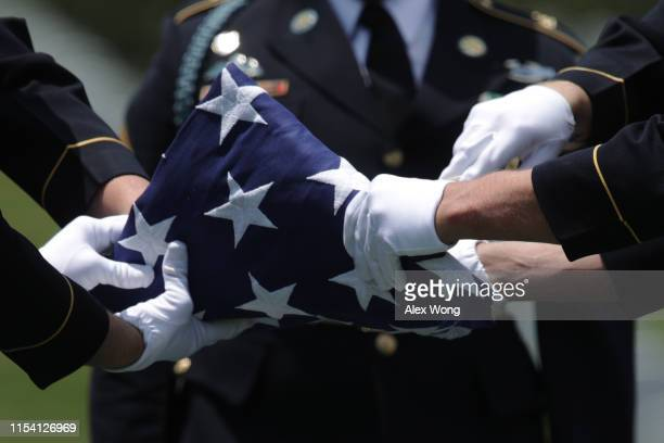 Members of the US Army's 3rd Infantry Regiment The Old Guard fold a flag during the funeral of World War II Army veteran Carl Mann on the 75th...