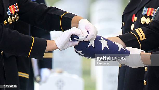 Members of the US Army's 3rd Infantry Regiment 'The Old Guard' fold the flag that covered the casket of Staff Sergeant Marc Arizmendez during his...