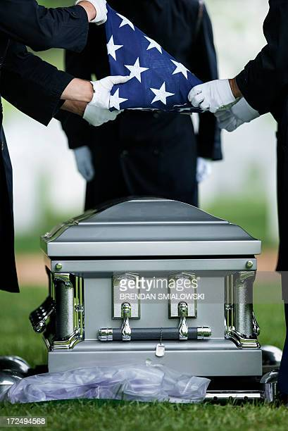 Members of the US Army's 3rd Infantry Regiment the Old Guard fold the American flag at a gravesite in Section 60 during a burial service at Arlington...