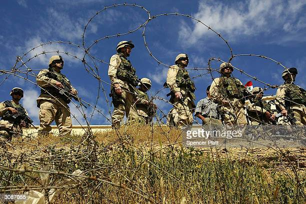 Members of the U.S. Army's First Armoured Division stand on the Iraqi side of the border with Iran March 15, 2004 at the Al-Munthriya border crossing...