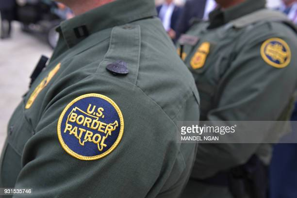 Members of the US Border Patrol listen as US President Donald Trump speaks after inspecting border wall prototypes in San Diego California on March...