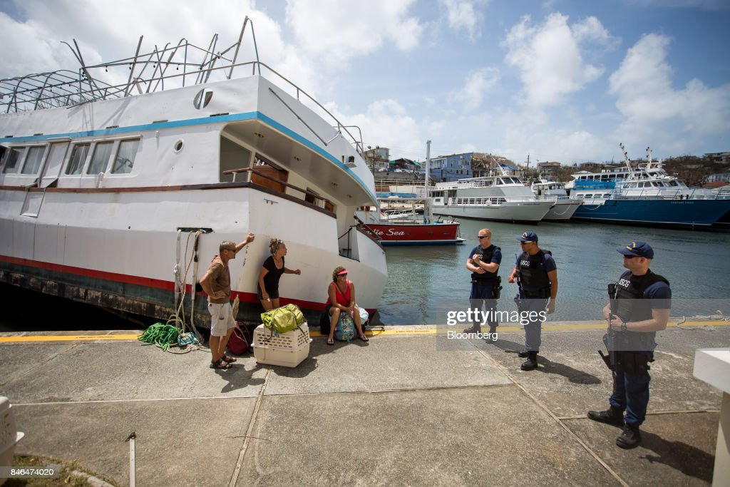 Members of the U.S. Coast Guard stand at an evacuation checkpoint after Hurricane Irma in St John, U.S. Virgin Islands, on Tuesday, Sept. 12, 2017. After being struck by Irma last week, the U.S. Virgin Islands couldnt look less like a tourist destination. Many local residents are giving up and getting out after losing everything to the category 5 storm,even as the local authorities in the U.S. territory say they are determined to rebuild the islands. Photographer: Michael Nagle/Bloomberg via Getty Images