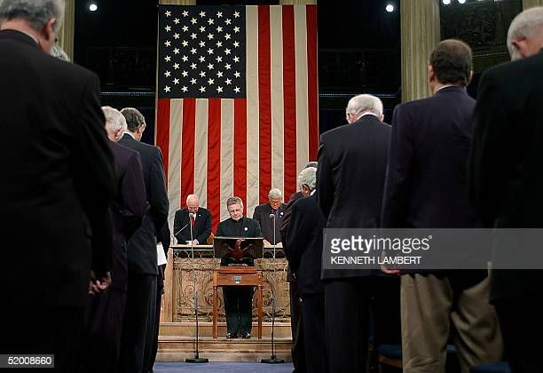 Members of the US Congress bow their heads as they listen to House Chaplain Daniel Coughlin say the invocation at the beginning of the commemorative...