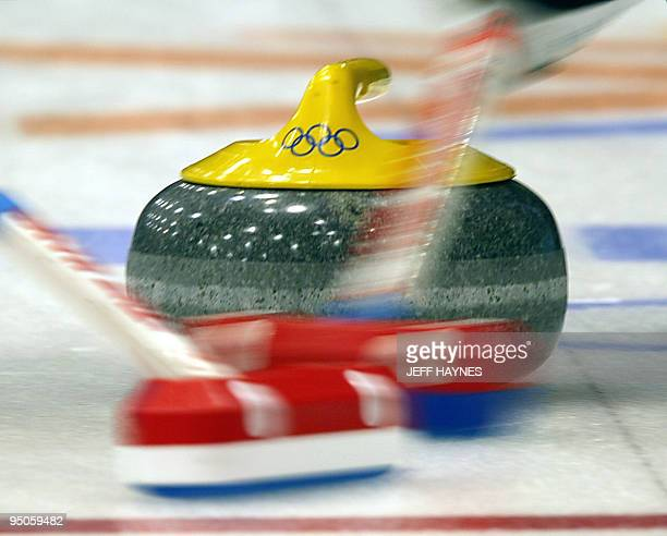 Members of the US curling team sweep in front of the stone 15 February 2002 during their team's match against France in the Men's curling at the Salt...