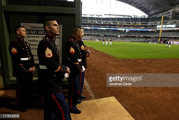 Members of the US Marine color guard watch batting practice from a gate in the right field wall before the home opener between the Atlanta Braves and...