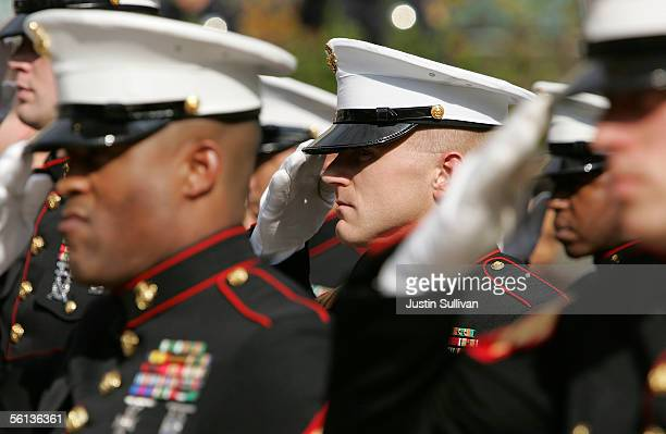 Members of the US Marine Corp honor guard salute during the singing of the National Anthem during the unveiling ceremony for the new Distinguished...