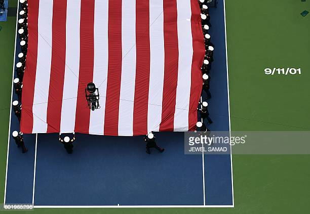 Members of the US Marine Corps Sixth Communications Battalion unfurl a large US flag across the Arthur Ashe Stadium before the start of the 2016 US...