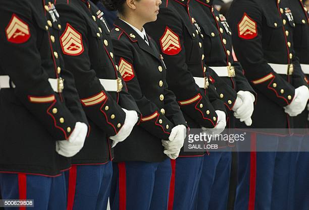 Members of the US Marine Corps stand as US First Lady Michelle Obama sorts toys and gifts donated by the Executive Office of the President staff to...