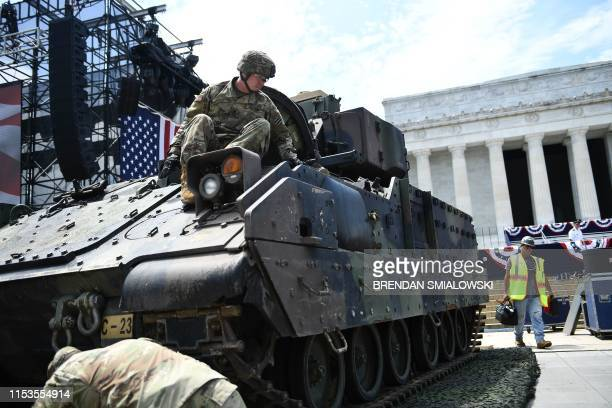 Members of the US military are seen next to a Bradley Fighting Vehicle as preparations are made for the Salute to America Fourth of July event with...