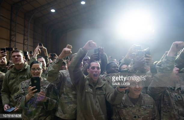 Members of the US military cheer as US President Donald Trump arrives to speak during an unannounced trip to Al Asad Air Base in Iraq on December 26...