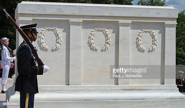 Members of the US Military Honor Guard stand in position shortly before Singapore Prime Minister Lee Hsien Loong places a wreath at the Tomb of the...