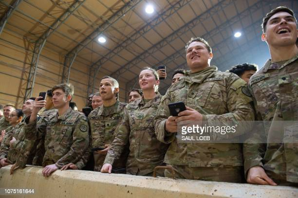 Members of the US military listen as US President Donald Trump speaks during an unannounced trip to Al Asad Air Base in Iraq on December 26 2018...