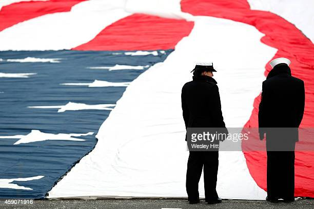 Members of the US military prepare a giant American flag for pregame activities before the Kansas City Chiefs vs Seattle Seahawks game at Arrowhead...