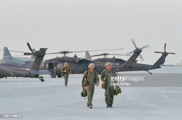 Members of the US Military wearing khaki overalls with three Sikorsky UH-60 Black Hawk helicopters grounded in the background during the liberation...