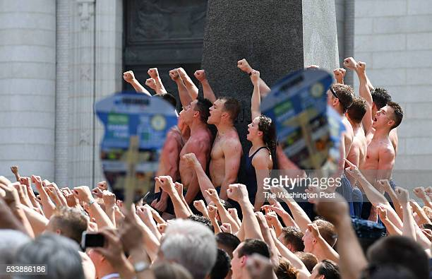 Members of the US Naval Academy 2019 class celebrate after forming a human pyramid and climbing the 21foot Herndon Monument covered in vegetable...