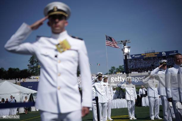 Members of the US Navy salute as they listen to the national anthem during a graduation ceremony at the NavyMarine Corps Memorial Stadium of the US...