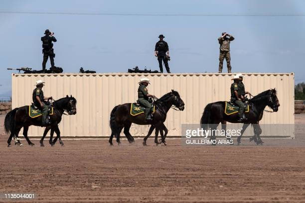 Members of the US secret service and border patrol agents on horseback patrol near the USMexico border fence in preparation for the visit of US...