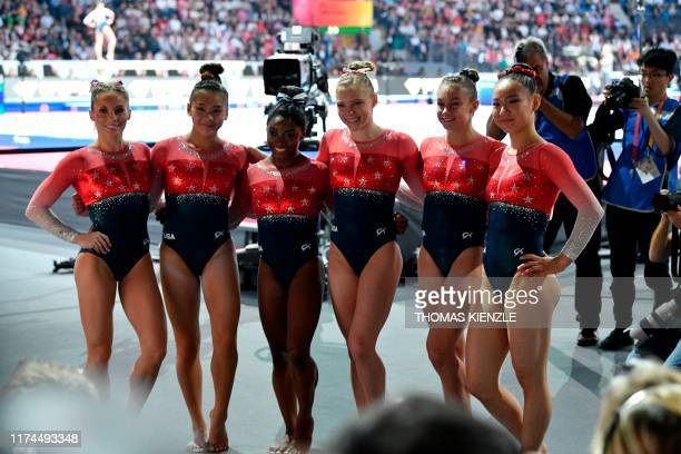 Members of the US team pose after winning the women's team final at the FIG Artistic Gymnastics World Championships at the HannsMartinSchleyerHalle...