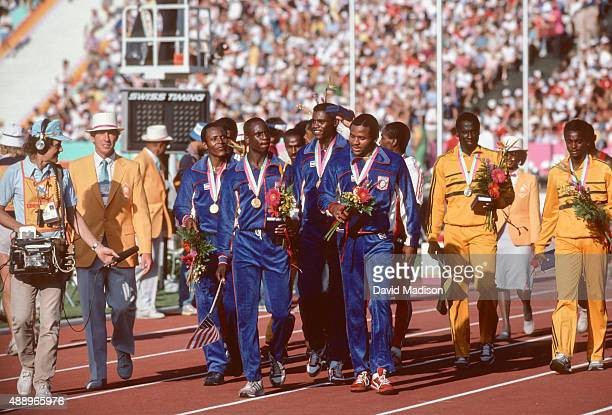 Members of the USA men's 4X100 meter relay team walk on the track following the medal ceremony at the 1984 Olympic Games on August 11 1984 in the Los...