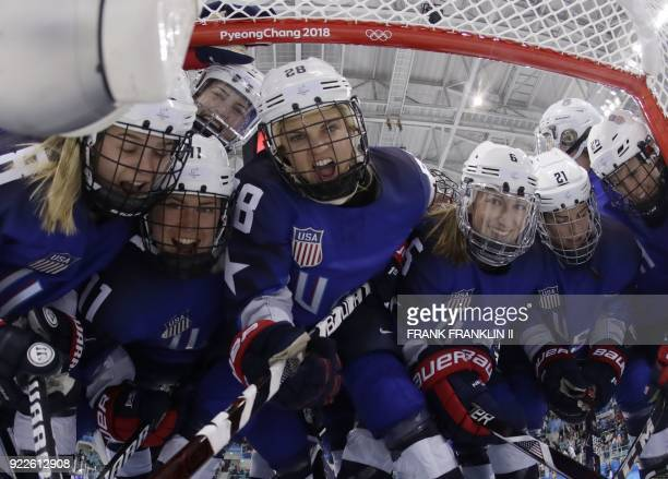 Members of the USA team gather in the net before the start of the women's gold medal ice hockey match between Canada and the US during the...