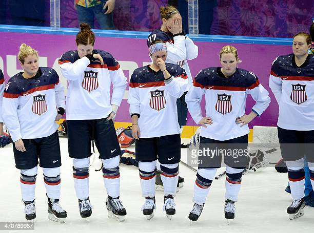 Members of the USA women's hockey team shed tears of disappointment as the wait for the medal ceremony to begin following a 32 overtime loss to...