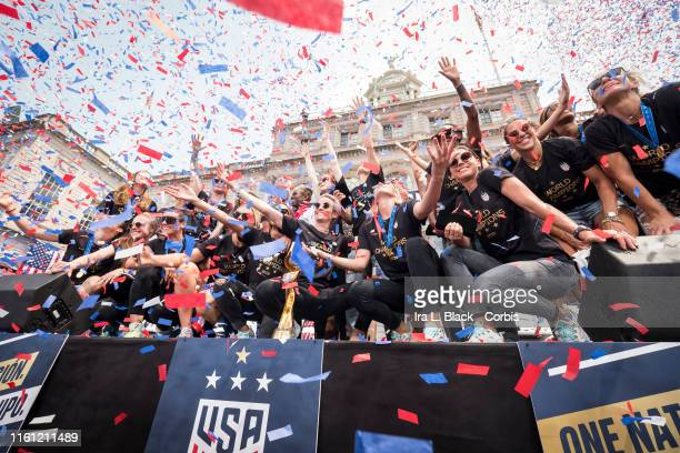 Members of the USA Women's National Soccer Team stand in front of the 2019 FIFA World Cup Trophy and get showered by confetti after the City Hall...