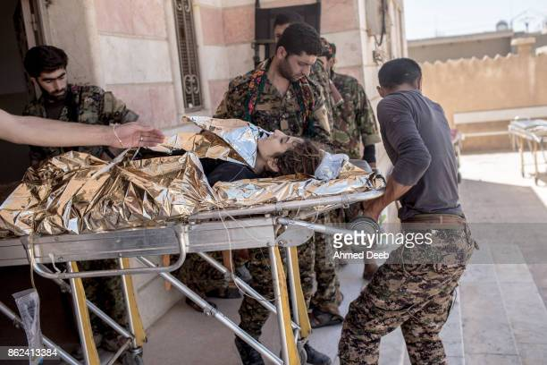 Members of the US-backed Syrian Democratic Forces carry a wounded woman at a military field hospital who was injured by a mine that exploded near...