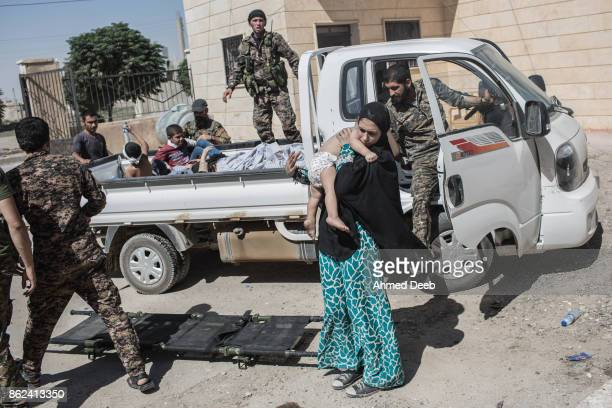 Members of the US-backed Syrian Democratic Forces carry an entire family who were injured by a mine that exploded near al-Mashlab neighborhood in the...