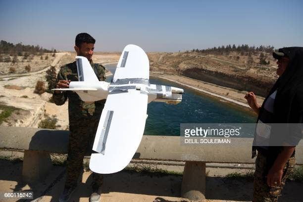 Members of the USbacked Syrian Democratic Forces made up of an alliance of Arab and Kurdish fighters inspect on March 29 2017 a downed drone...