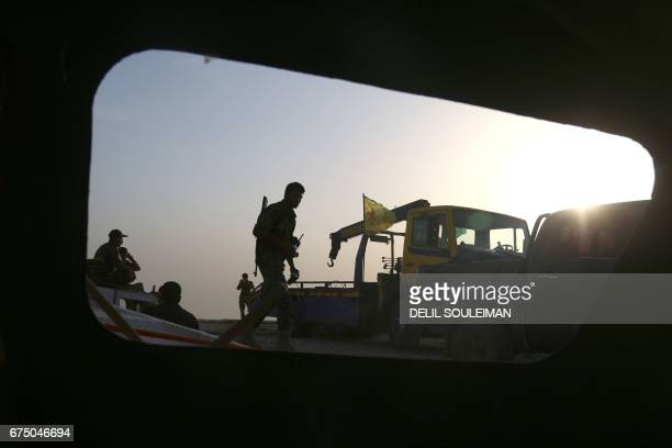 TOPSHOT Members of the USbacked Syrian Democratic Forces made up of an alliance of Arab and Kurdish fighters patrol next to boats at the Lake Assad...