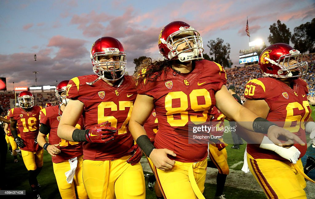 Members of the USC Trojans run off the field after warmups for the game with the UCLA Bruins at the Rose Bowl on November 22, 2014 in Pasadena, California.