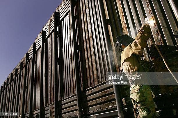 Members of the Utah Army National Guard unit 1457 build new portions of the border fence along the ArizonaMexico border June 15 2006 in San Luis...