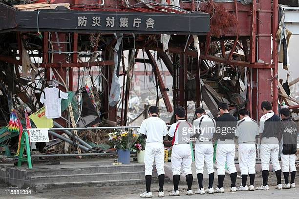 Members of the Utatsu Junior High School baseball team pray for their coach who went missing at Minamisanriku City Hall Disaster Prevention Center in...