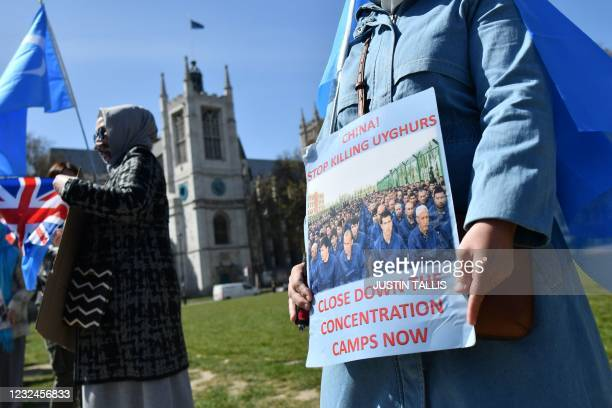 Members of the Uyghur community hold a placard and the flag adopted by the East Turkestan independence movement as they demonstrate to call on the...
