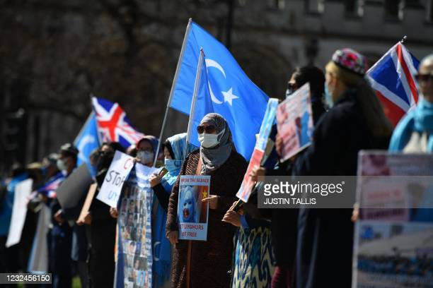 Members of the Uyghur community hold the flag adopted by the East Turkestan independence movement and placards as they demonstrate to call on the...