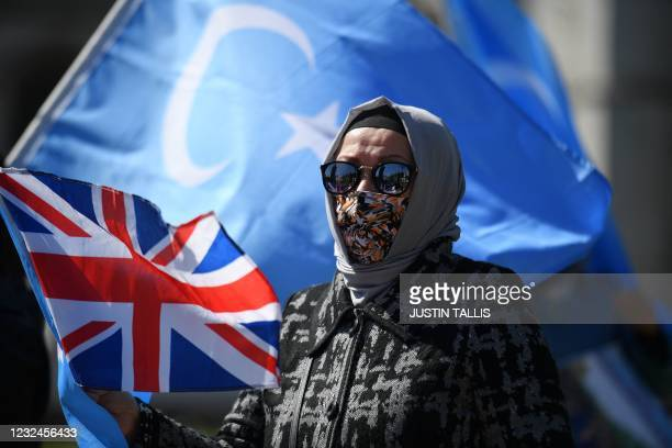 Members of the Uyghur community hold the flag adopted by the East Turkestan independence movement and the Union Flag as they demonstrate to call on...
