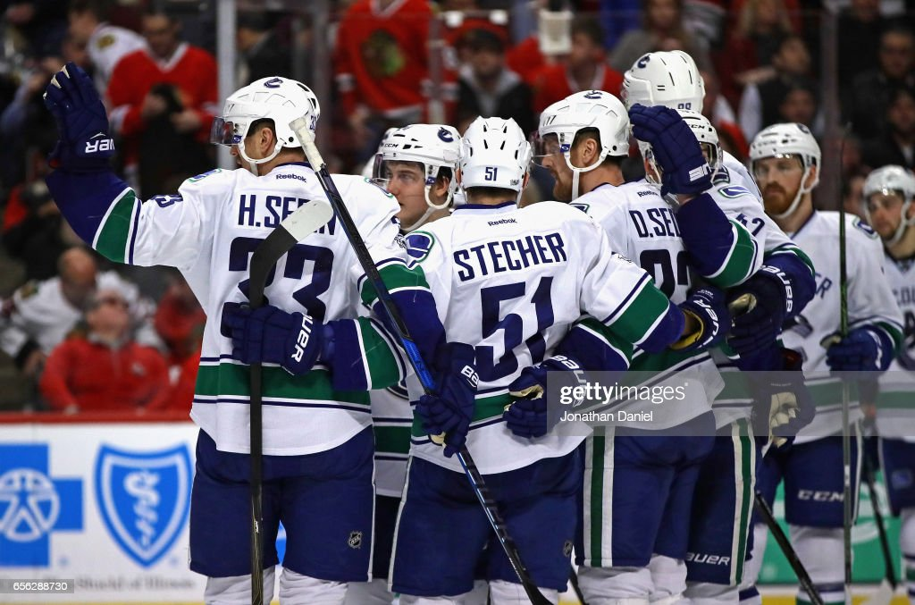 Members of the Vancouver Canucks including Henrik Sedin #33, Troy Stecher #51 and Daniel Sedin #22 celebrate after a win over the Chicago Blackhawks at the United Center on March 21, 2017 in Chicago, Illinois. The Canucks defeated the Blackhawks 5-4 in overtime.