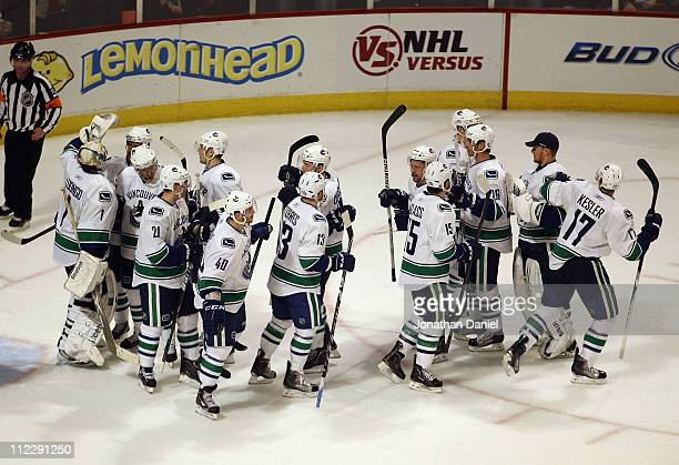 Members of the Vancouver Canucks including Roberto Luongo Mason Raymond Maxim Lapierre and Raffi Torres celebrate a win over the Chicago Blackhawks...