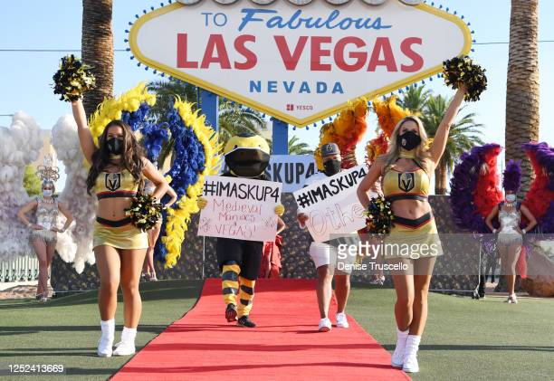 Members of the Vegas Golden Knights Vegas Vivas flank the team's mascot Chance the Golden Gila Monster and singer Carnell Johnson as they participate...