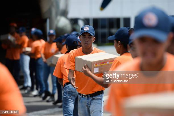 TOPSHOT Members of the Venezuelan Civil Protection load supplies with humanitarian aid for the island of Dominica after the Caribbean island was...