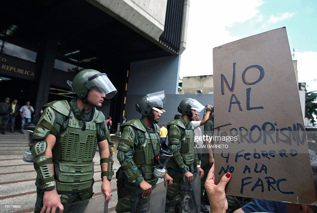 Members of the Venezuelan militarized police stand guard in front of the public prosecutor?s office as demonstrators hold a sign against the Revolutionary Armed Forces of Colombia (FARC) during a protest against Venezuelan president Hugo Chavez 23 January, 2008 in Caracas. The Venezuelan government commemorated today the 50th anniversary of the fall of the last dictatorship -gen. Marcos Perez Jimenez (1948-58). AFP PHOTO/Juan BARRETO