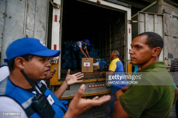 Members of the Venezuelan Red Cross distribute drums to collect water and water purification tablets in Caricuao neighborhood in Caracas Venezuela on...
