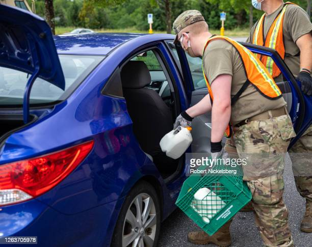 Members of the Vermont National Guard load boxes of food into a private car during an event sponsored by the Guard and the Vermont Food Bank on...