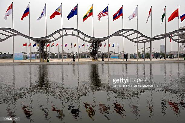 Members of the Vietnamese security forces patrol past flags of the participating countries at the venue of the upcoming 17th ASEAN Summit and Related...