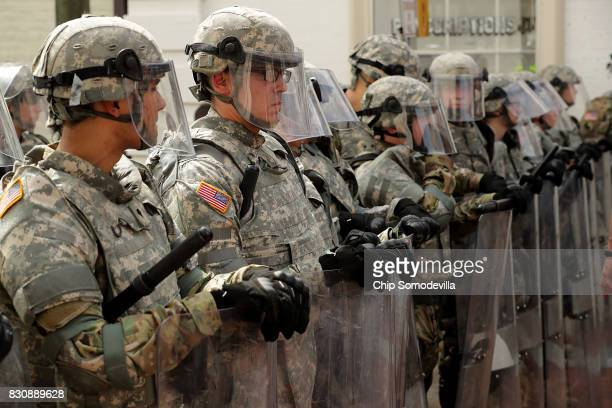 Members of the Virginia National Guard wear body armor and carry riot shields while standing guard on the pedestrian mall following violence at the...