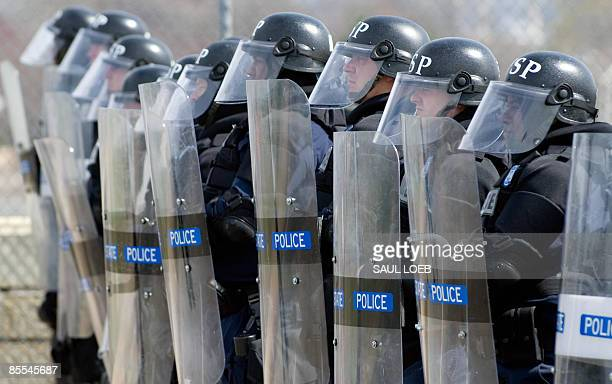 Members of the Virginia State Police dressed in riot gear stand guard near the Pentagon as thousands of demonstrators march to the Pentagon during...