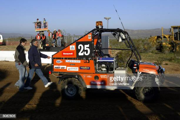 Members of the Virginia Tech team approach Cliff, their autonomous, or un-manned, vehicle, after its brake locked-up near the starting line in a...