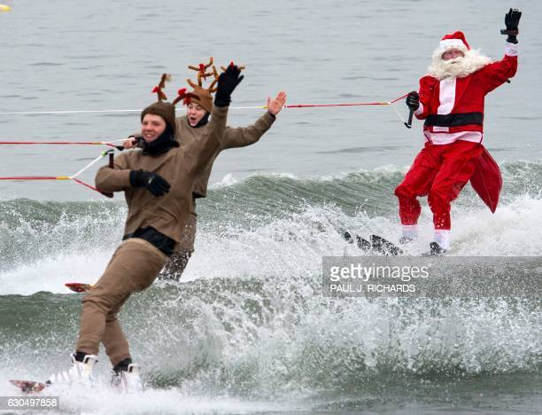 TOPSHOT Members of the volunteer Water Skiing Christmas Show including a water skiing Santa Claus with elves reindeer the Grinch and others water ski...