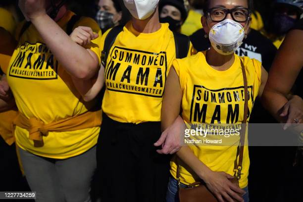 Members of the Wall of Moms a group of protesters who form nonviolent human barriers between police and the crowd stand arm in arm during a protest...